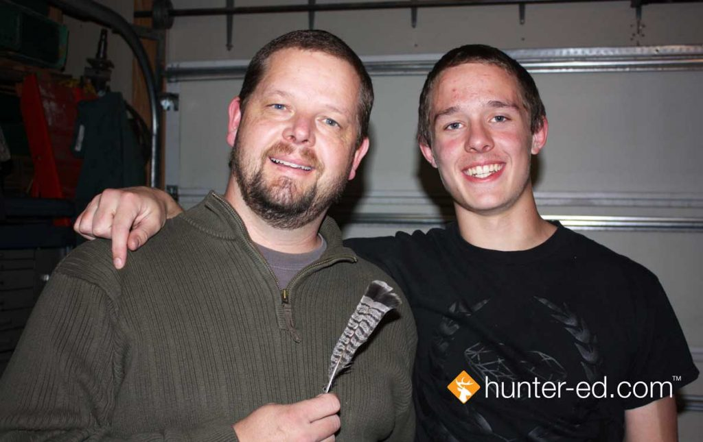 Hunter education instructor Randy Allen with his son and the grouse feather they received as a gift.